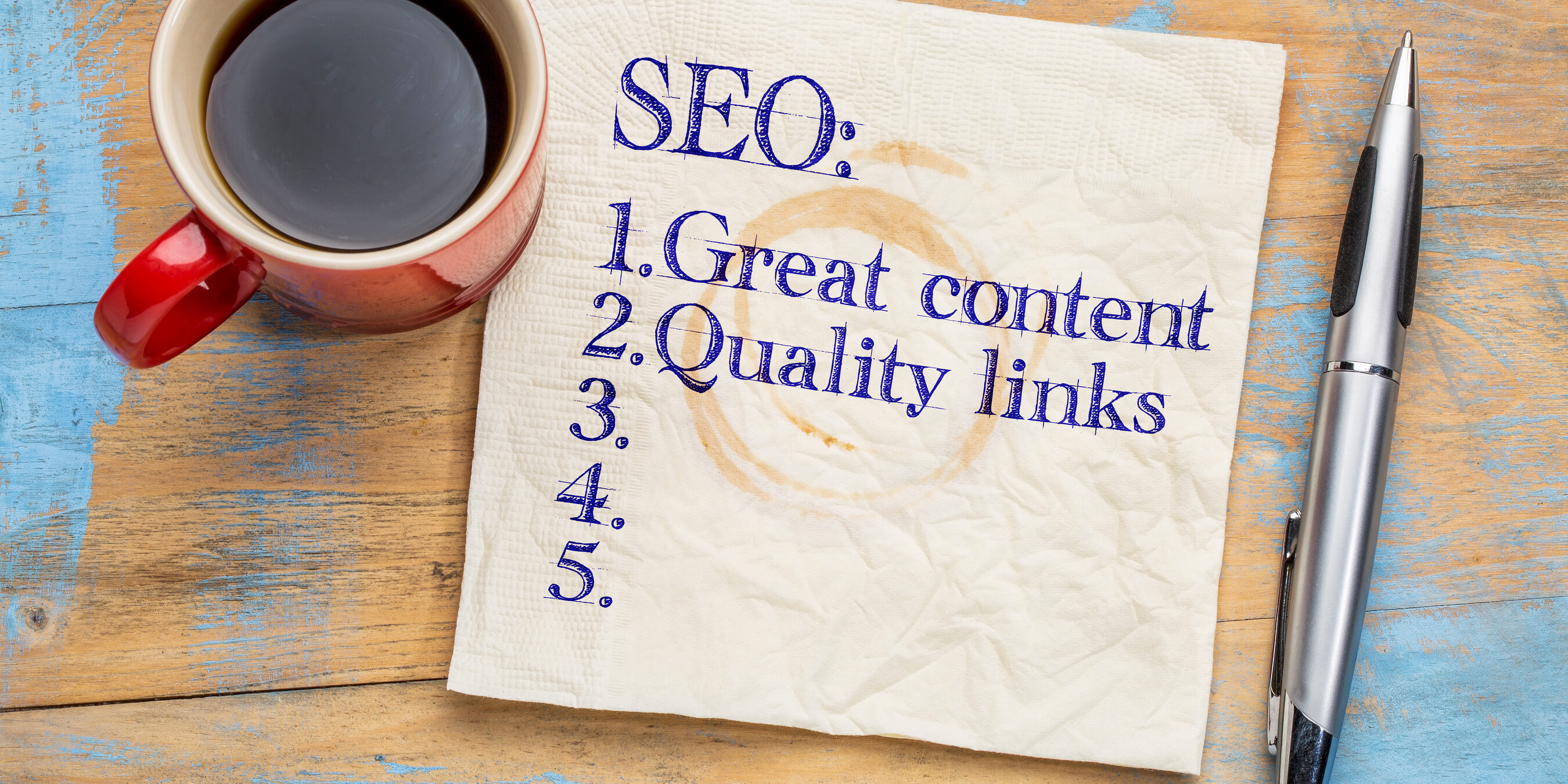 SEO (search engine optimization) tips (great content and quality links) written on napkin with a cup of coffee | Vanguard Communications | Denver, CO