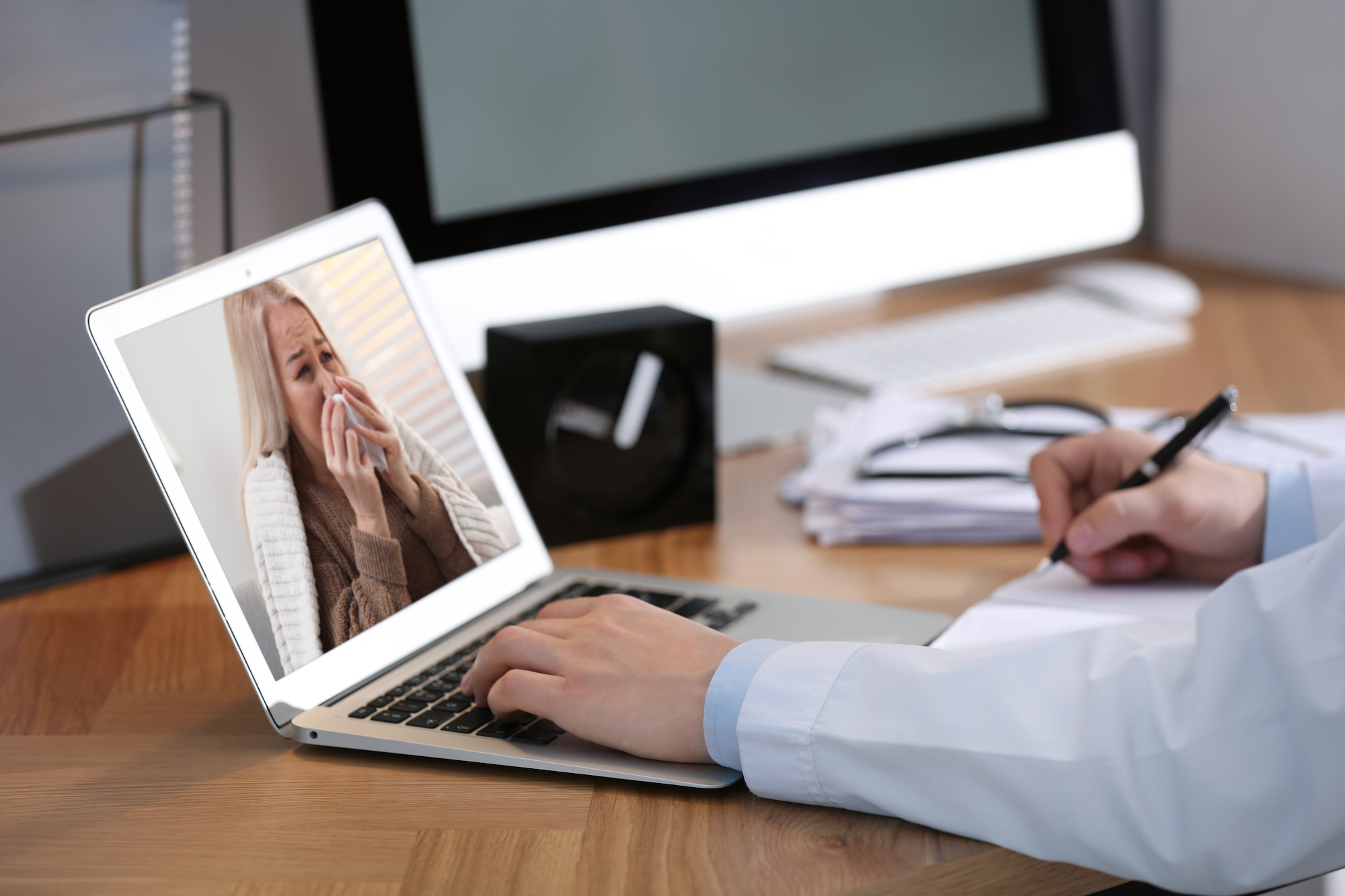 Doctor using proper netiquette for telehealth at laptop with a sick patient on the screen | Vanguard Communications | Denver, CO | San Jose, CA