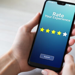 Hands holding cellphone and selecting 5 star rating | Vanguard Communications | Denver, CO