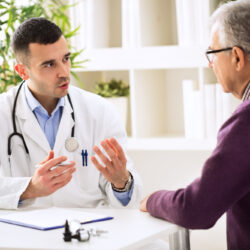 Physician seated speaking to man, enhancing the doctor patient relationship | Vanguard Communications | Denver, CO