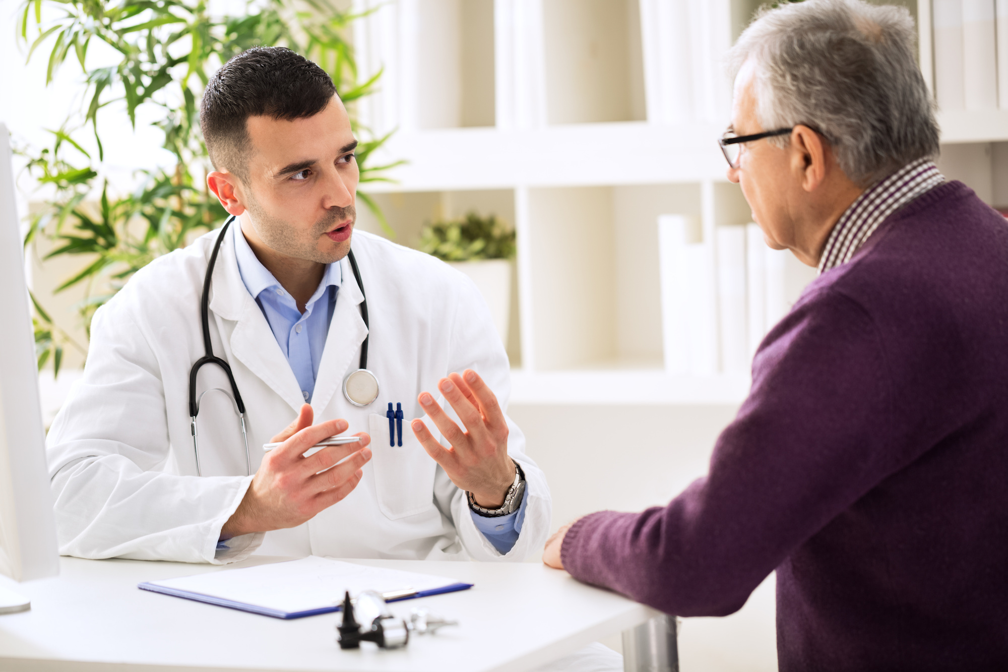 Physician seated speaking to man enhancing the doctor patient relationship | Vanguard Communications | Denver, CO