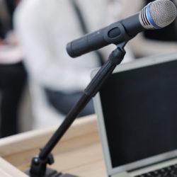 Blogging for patient trust | Vanguard Communications | Microphone on podium