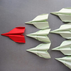 Beating meeting defeaters | Vanguard Communications | Red and white paper airplanes