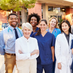 Medical team standing outside hospital in blog illustrating nonmonetary methods of employee motivation | Vanguard Communications | Denver, CO