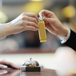 Hotel receptionist giving a guest her room key, a lesson from the hospitality industry on healthcare customer service | Vanguard Communications | Denver