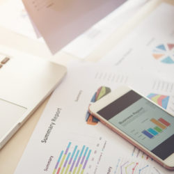 Embrace Medical Marketing | Vanguard Communications | Denver | doctor using laptop, smartphone and marketing charts